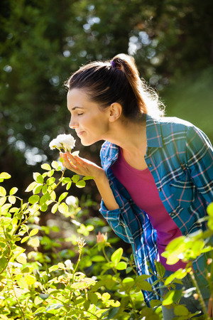 back ache: Smiling woman with closed eyes smelling white roses at backyard