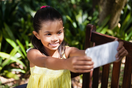 back ache: Smiling girl taking selfie while sitting on wooden bench at backyard Stock Photo