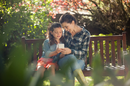 back ache: Girl showing mobile phone to mother while sitting on wooden bench at backyard