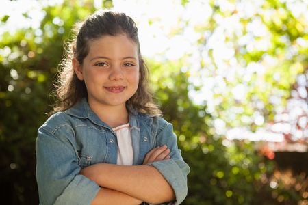 back ache: Portrait of confident girl with arms crossed standing against plants in backyard Stock Photo