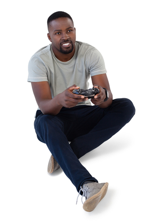 Smiling man playing video game against white background