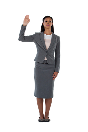 Businesswoman raising her hand against white background