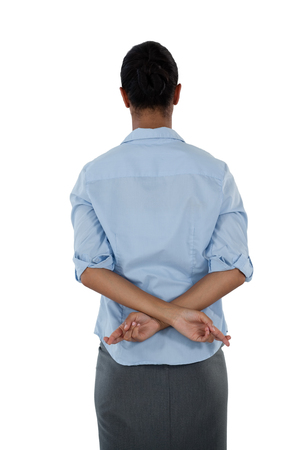 Achtermening van onderneemster die haar vingers achter haar rug gekruist houden