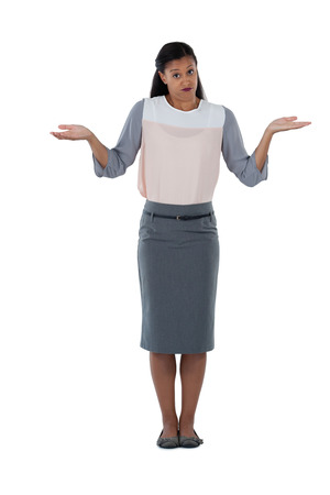 Frowning businesswoman shrugging her shoulders against white background