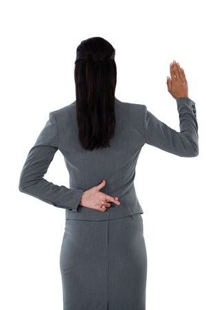 Rear view of businesswoman raising her hand against white background Stock Photo