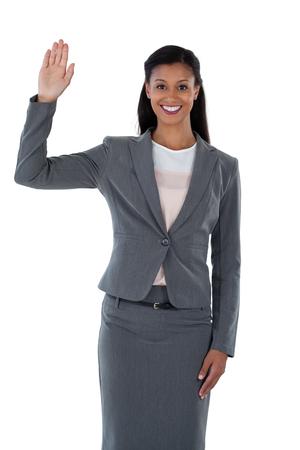Businesswoman raising her hand against white background