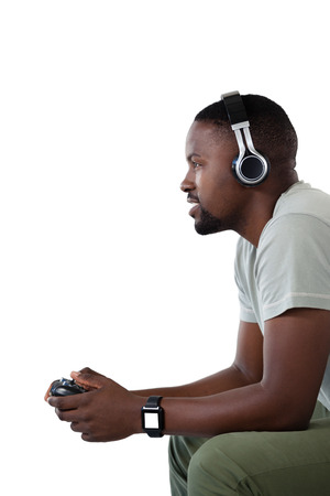 electronic music: Side view of man playing video game against white background