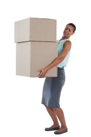 Businesswoman carrying heavy boxes against white background