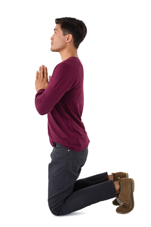 Side view of business praying while kneeling against white background