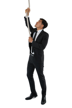 conquering adversity: Businessman pulling rope while standing against white background