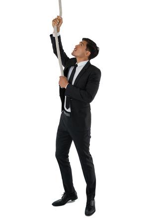 carretilla: Empresario tirando de la cuerda mientras está de pie contra el fondo blanco Foto de archivo