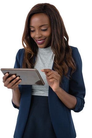 Happy businesswoman using tablet computer while standing against white background