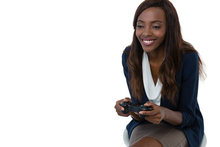 sit down: Smiling businesswoman playing video game while sitting on stool against white background