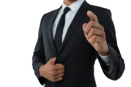 Mid section of businessman pointing while standing against white background Stock Photo