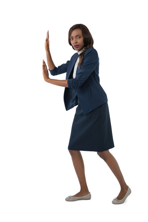 Portrait of young businesswoman pushing something on white background
