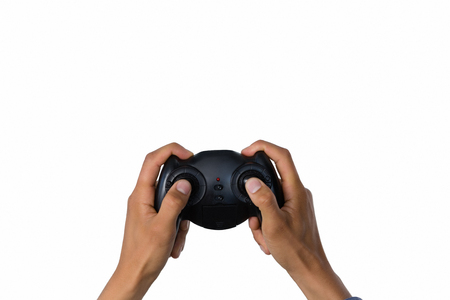 Cropped image of hand holding controller against white background