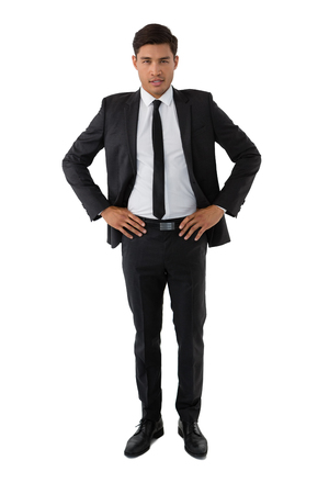 Portrait of young businessman with hand on hip standing against white background