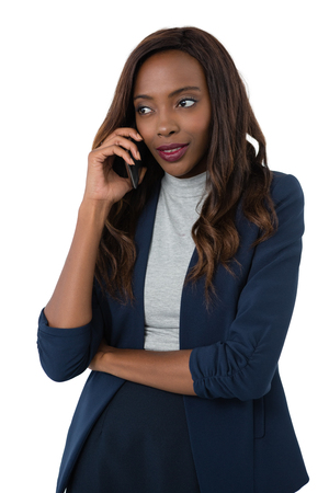 Woman looking away while talking on mobile phone against white background