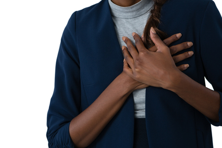 Mid section of woman suffering from chest pain against white background