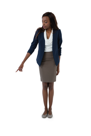 Full length of businesswoman pointing while standing against white background Stock Photo