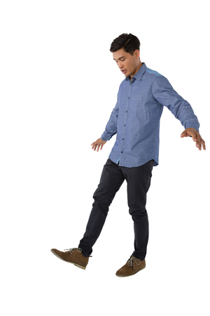 Full length of man looking at shoe while standing against white background Stock Photo