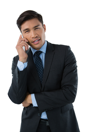 Portrait of businessman talking on smartphone while standing against white background