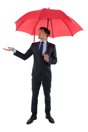 Full length of businessman holding umbrella while standing against white background