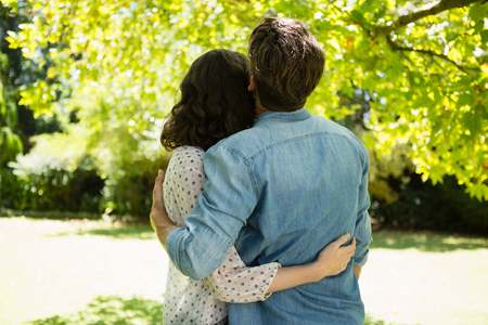 Rear view of couple embracing each other in garden on a sunny day