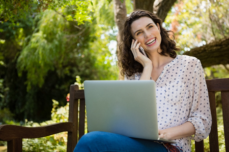 Woman talking on mobile phone while using laptop in garden