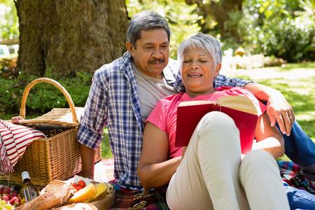 Senior couple reading book at the park Stock Photo