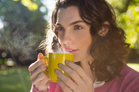 Thoughtful woman having a cup of coffee in garden Stock Photo