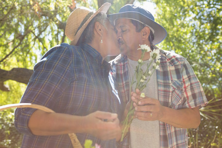 Senior couple kissing in garden with flower basket in the park
