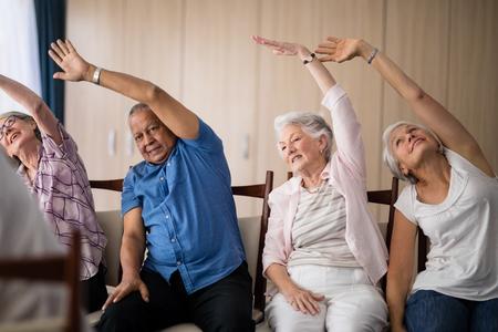 Personas mayores que se extiende mientras que se sienta en sillas en la casa de retiro