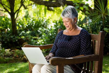 Senior woman using laptop in the garden