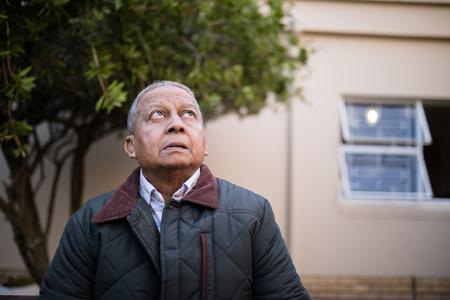 Retired senior man looking up against nursing home