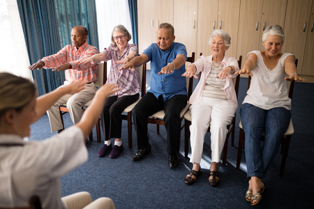Female doctor exercising with senior people at retirement home