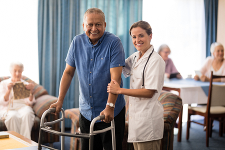 70s: Portrait of smiling female doctor standing by senior man with walker at retirement home Stock Photo