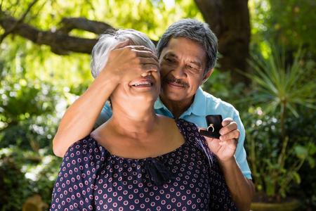Senior man covering woman eyes while gifting her ring in garden