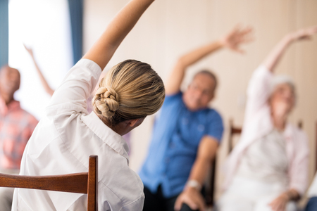 Rear view of female doctor stretching with senior people at retirement home Stock Photo