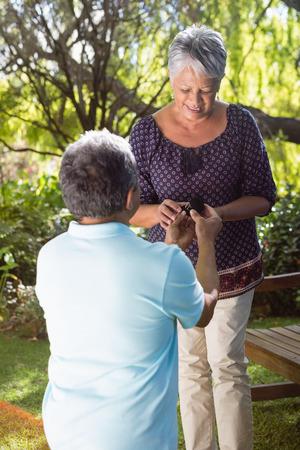 Senior man proposing woman by gifting ring in garden