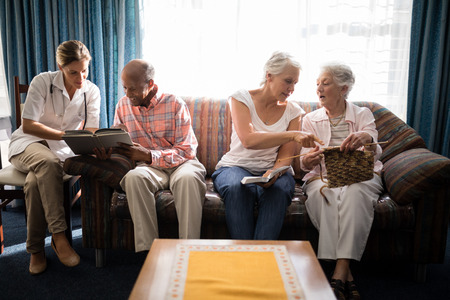 Female doctor reading book with man while senior women talking against window at retirement home