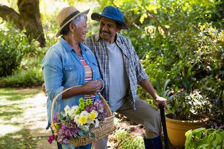 Senior couple walking in garden with flower basket