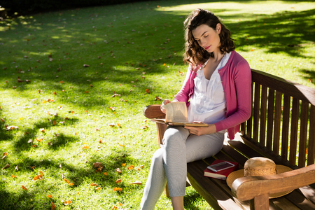 Woman sitting on bench and reading book at the garden Stock Photo