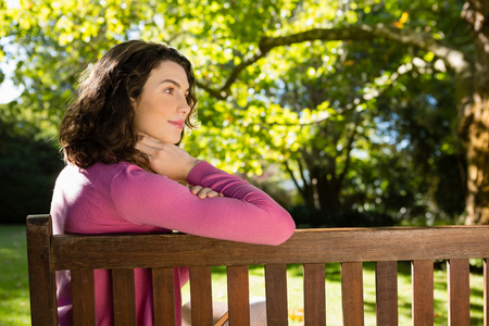 Woman sitting on bench in garden on a sunny day