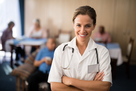 Portrait of smiling female doctor standing with arms crossed at retirement home