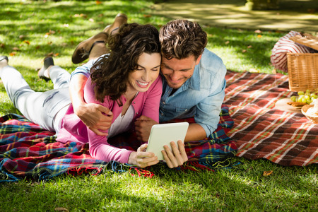 Couple lying on picnic blanket and using digital tablet in park