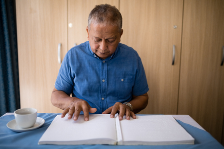 Senior man reading book at table in retirement home