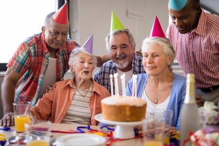 Happy senior people wearing party hats celebrating birthday at nursing home