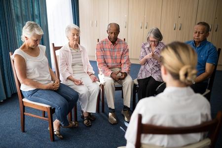 Personnes âgées qui méditent avec une femme médecin à la maison de retraite Banque d'images - 82661900