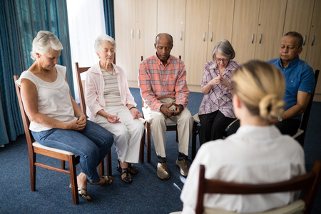 Senior people meditating with female doctor at retirement home Stock Photo